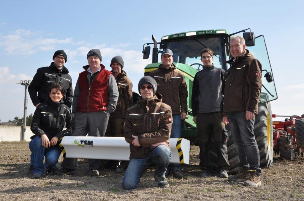 Zufriedene Kundenvor einem Traktor mit Topsoil Mapper am Feld