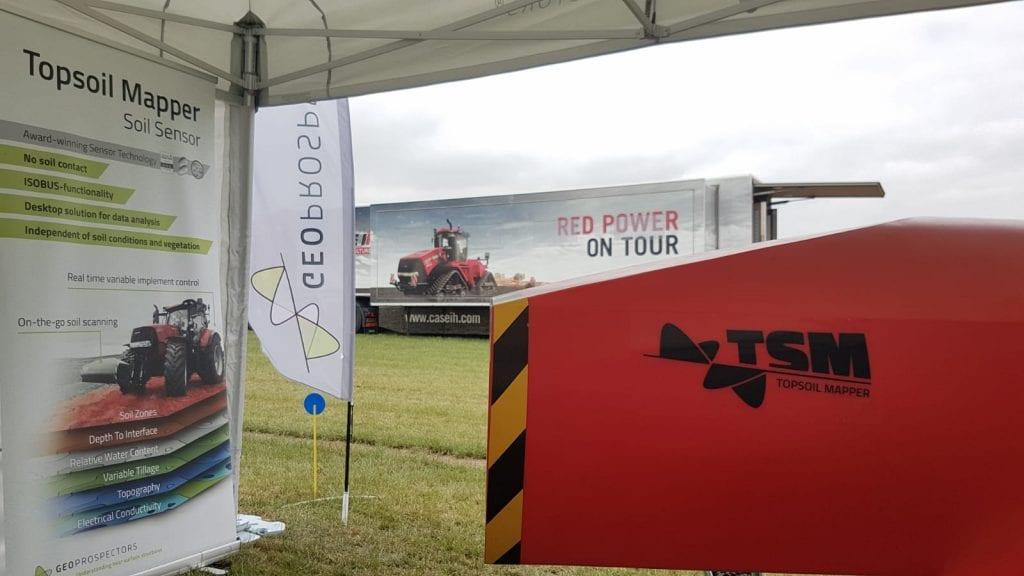 Ausstellung eines roten Topsoil Mappers mit Innovationen auf einem Banner